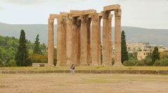 Tourists posing near tall Corinthian columns of the Temple of Olympian Zeus Stock Footage