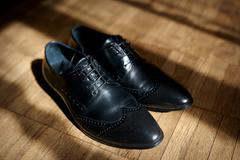 Pair of men's black leather ankle shoes placed on wooden floor Stock Photos