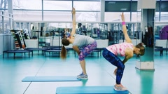 Two girls do yoga - show different poses and freeze Stock Footage