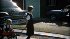 1957: Girl pulled around in red wagon on the new suburban sidewalk. Stock Footage
