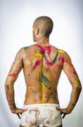 Back of shirtless young man, skin painted all over with bright Holi colors - stock photo