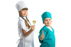 Cute girl and boy doctor in uniform standing isolated on white background - stock photo