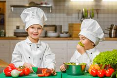 Funny happy chef boys cooking at restaurant kitchen. concept of vegetarianism - stock photo