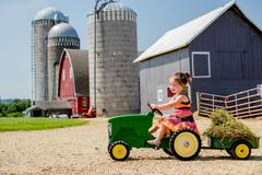 Elementary aged girl driving her toy tractor Stock Photos