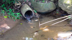 Open sewer at natural river Stock Footage
