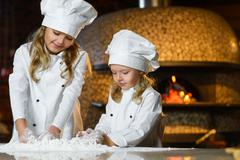Funny happy chef boy width girl cooking at restaurant kitchen and knead the Stock Photos