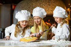 Cute smiling girl chef admiring look at pizza Stock Photos