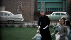 1957: Catholic priest supervising an Easter egg hunt in the church courtyard. - stock footage