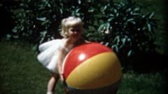 1957: Young blonde girl playing with oversized beach ball. Stock Footage