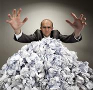 Serious businessman reaches out from crumpled papers Stock Photos