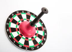 Dart board with plunger on white background Stock Photos