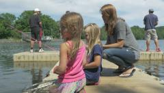 Little girls fish with mother off a lakeside dock Stock Footage