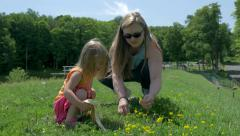 Mother picks flowers with daughter near lake Stock Footage