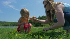 Stock Video Footage of Mother picks flowers with daughter near lake - alternate