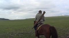 Stock Video Footage of Man Rides on Horseback in The Midst of The Vast Mongolian Steppe