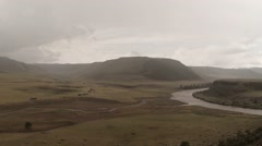 river flows under the cloudy sky in the mountains of Mongolia - stock footage