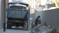 Shovelling rubble, manual workers, China - stock footage