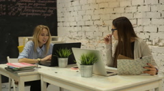 Two smilling businesswomen working on laptop at office - stock footage