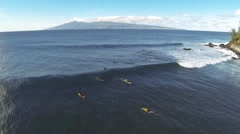 Aerial shot of sufers in Hawaii catching waves, surfing, and wiping out. - stock footage