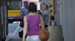 People standing next to a bus parked on a street in Warsaw Stock Footage