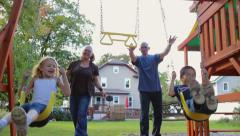 Mom and dad pull kids back on swing and let them go Stock Footage