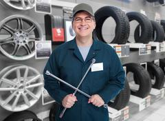 Car mechanic with tire wrench. - stock photo
