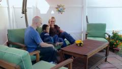 Mom brings toy truck over to father and son sitting on patio Stock Footage