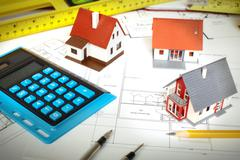 Little house and calculator on the table. - stock photo
