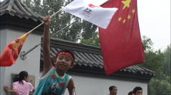 Chinese boy waving flags, Beijing Olympics Stock Footage