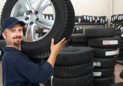 Car mechanic with a tire. - stock photo