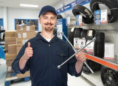 Car mechanic with tire wrench. Stock Photos