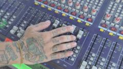 Pan down to tattooed hand on audio board Stock Footage