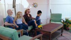 Boy plays with toy truck as family sits on patio Stock Footage