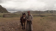 Mongolian man in national dress with a horse on a background of hills and Stock Footage