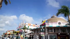 Walking in front of the colorful Royal Plaza Mall in Oranjestad Aruba Stock Footage