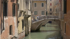 A small group of people walking on a bridge over a canal of Venice - stock footage