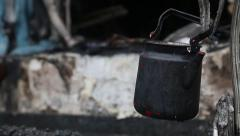 Black kettle on charred ruins in burnt building Stock Footage