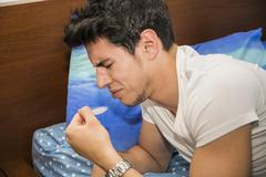 Young Man in Bed Disgusted by Cough Syrup - stock photo