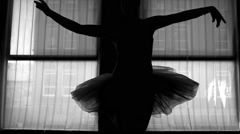 Black and white silhouette of a ballerina dancing in front of a window Arkistovideo