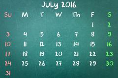Green blackboard wall texture with a word Calender 2016 July Stock Photos