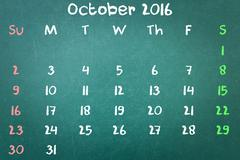 Green blackboard wall texture with a word Calender 2016 October - stock photo