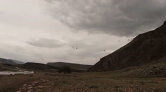 Stock Video Footage of Mongolian small river close to the rocks and mountains under cloudy sky