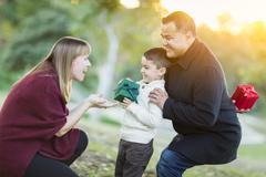 Stock Photo of Happy Young Mixed Race Son Handing Gift to His Mom As Father Stands Behind.