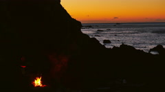 A campfire on the coast with a beautiful view of the sunset Stock Footage
