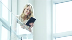 Blonde Caucasian businesswoman seeing news of success on wireless tablet device - stock footage
