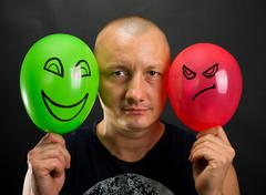 Emotionless man between happy and angry balloons - stock photo