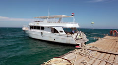 Stock Video Footage of Pleasure white ship for sea cruises is moored on pier. Boat trips in the Red Sea