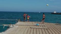Children run on wooden pier near the moored pleasure ship for sea cruises. Egypt Stock Footage