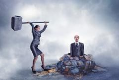 Businesswoman with sledgehammer banging scared worker into the ground Stock Photos