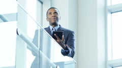 African American male business advisor using wifi tablet in the city atrium - stock footage